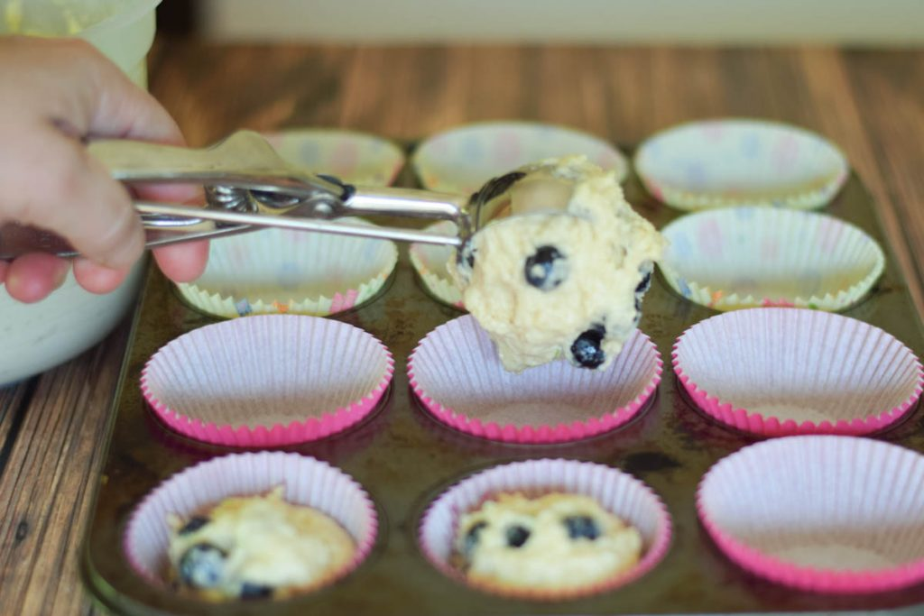 scooping the muffin batter into paper lined muffin pan