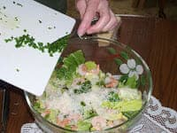 adding chopped chives to the salad