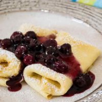 2 cheese blintzes on a plate with blueberry sauce