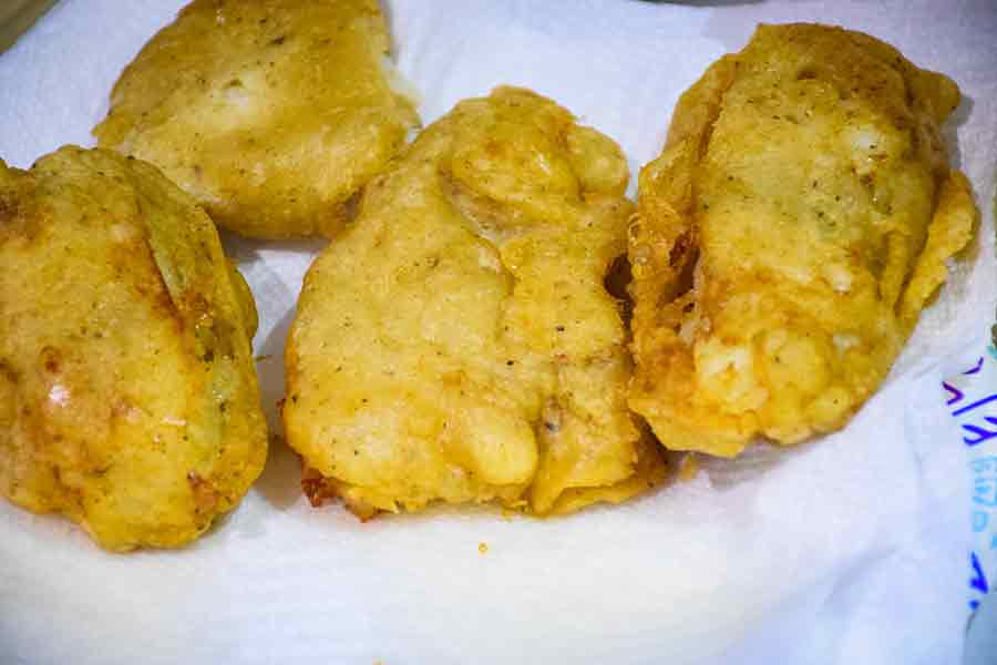 Beer Battered Fish draining on paper towel lined plate