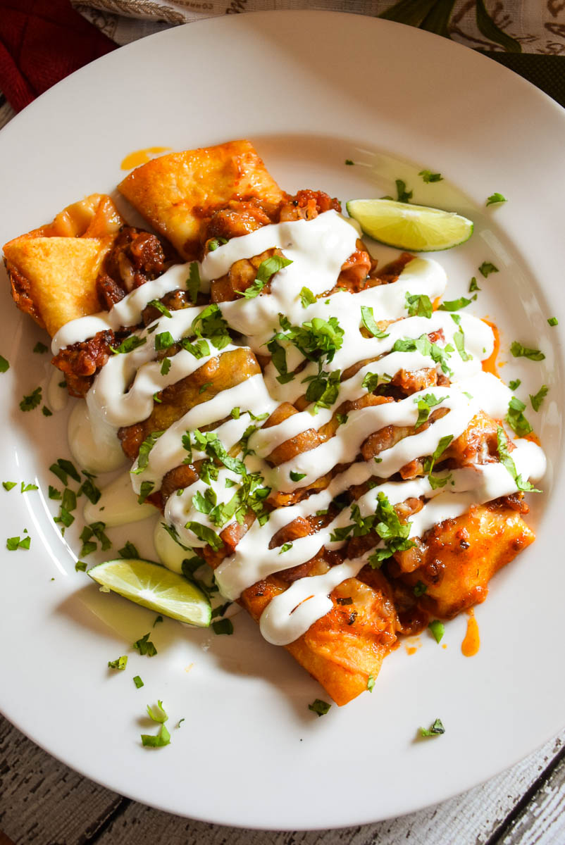 Overhead view of two Cheese Enchiladas with Red Sauce on a white plate