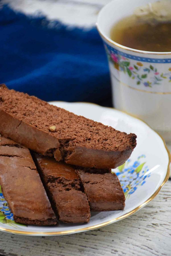 Brownie Biscotti on a plate with a cup of tea in the background
