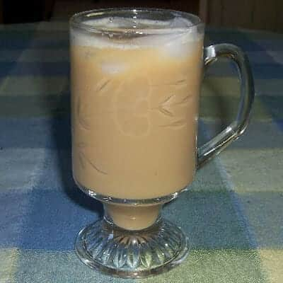 A clear crystal glass with iced coffee and pieces of ice floating on the top.