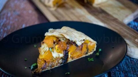 A slice of butternut squash galette on a black plate