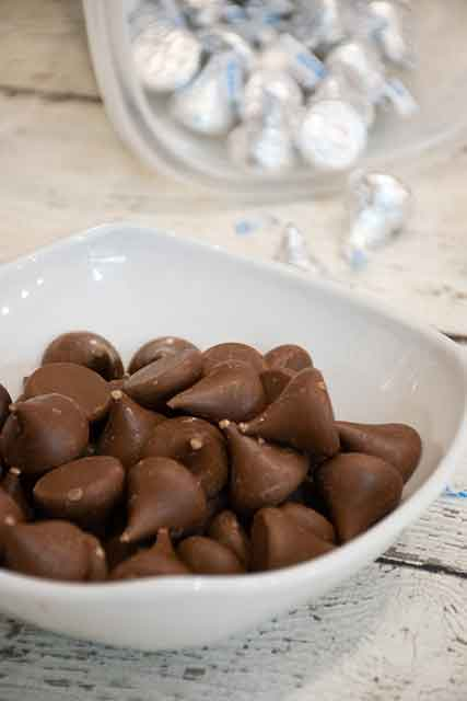 Unwrapped Hershey Kisses in a white bowl with wrapped kisses in the background