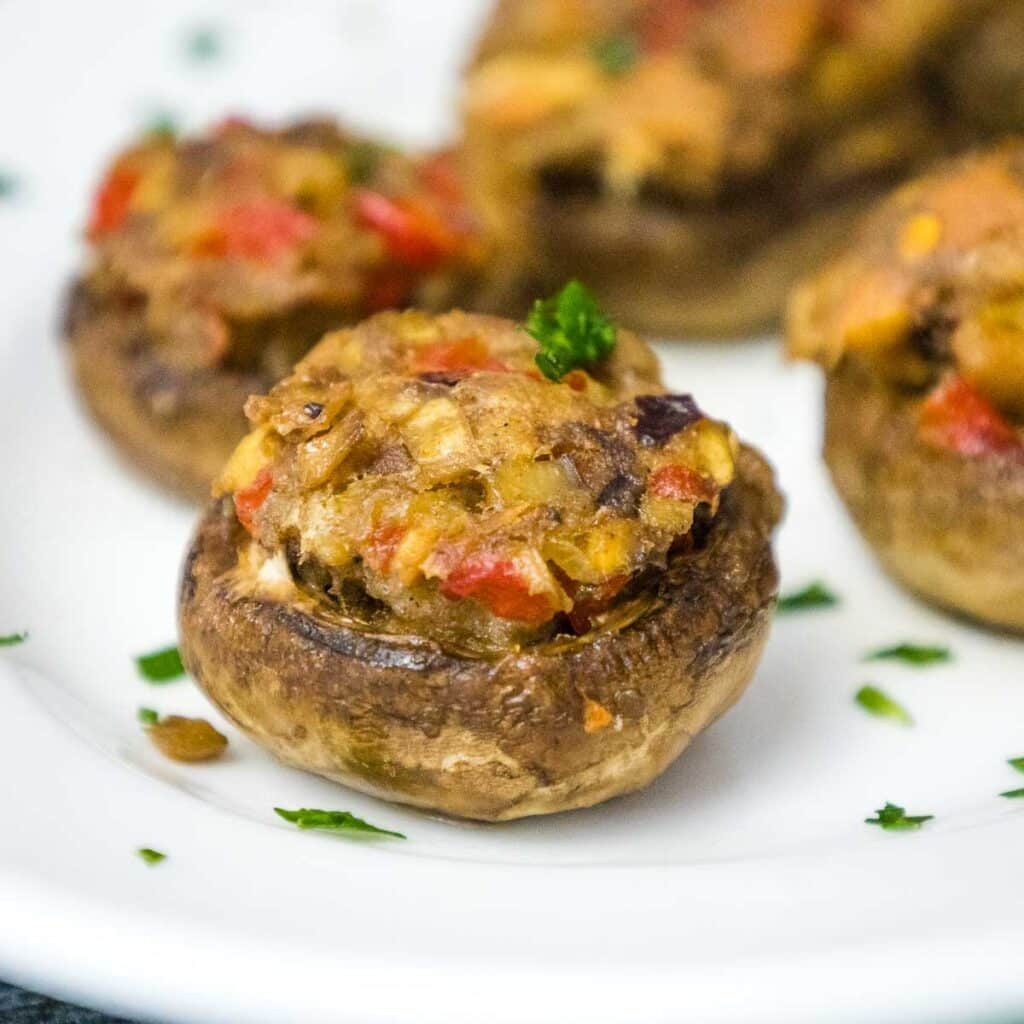 A white plate with one stuffed mushroom in the front and 3 more stuffed mushrooms blurred in the background with flecks of green chopped parsley sprinkled over top of the mushrooms and some parsley on the plate.