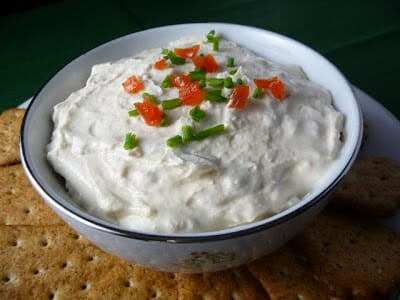 Clam Dip in a white bowl with red  pepper and green onion top garnish