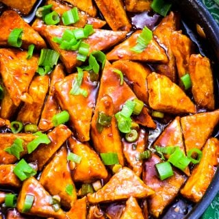 Overhead skillet view of Triangular shapes of crispy general tso's tofu coated in sauce and sprinkled with green onion tops.