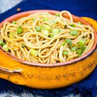 Garlic Scallion Noodles in an orange bowl with a blue napkin