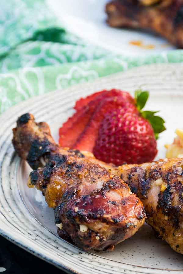 Grilled Apricot Glazed Chicken Legs on a plate with a strawberry in the background
