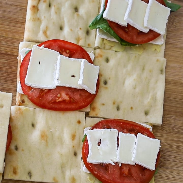 Square cut Naan Flatbread pieces with red tomato, white brie cheese and green fresh basil on top of 3 of the slices.