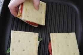 Placing a sandwich on the grill pan.
