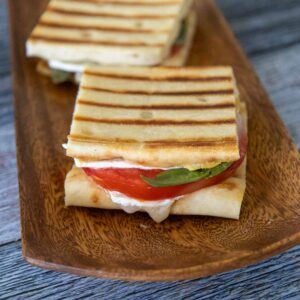 Two grilled brie tomato sandwichs made with flatbread with brie cheese, red tomato, and green fresh basil on a brown serving tray.