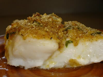 Thick red snapper fillet on a red plate with bread crumb topping.