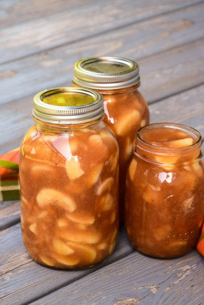 Two quart sized jars and one pint sized jar of homemade apple pie filling on a rustic wood plank with a orange and green plaid napkin in the background