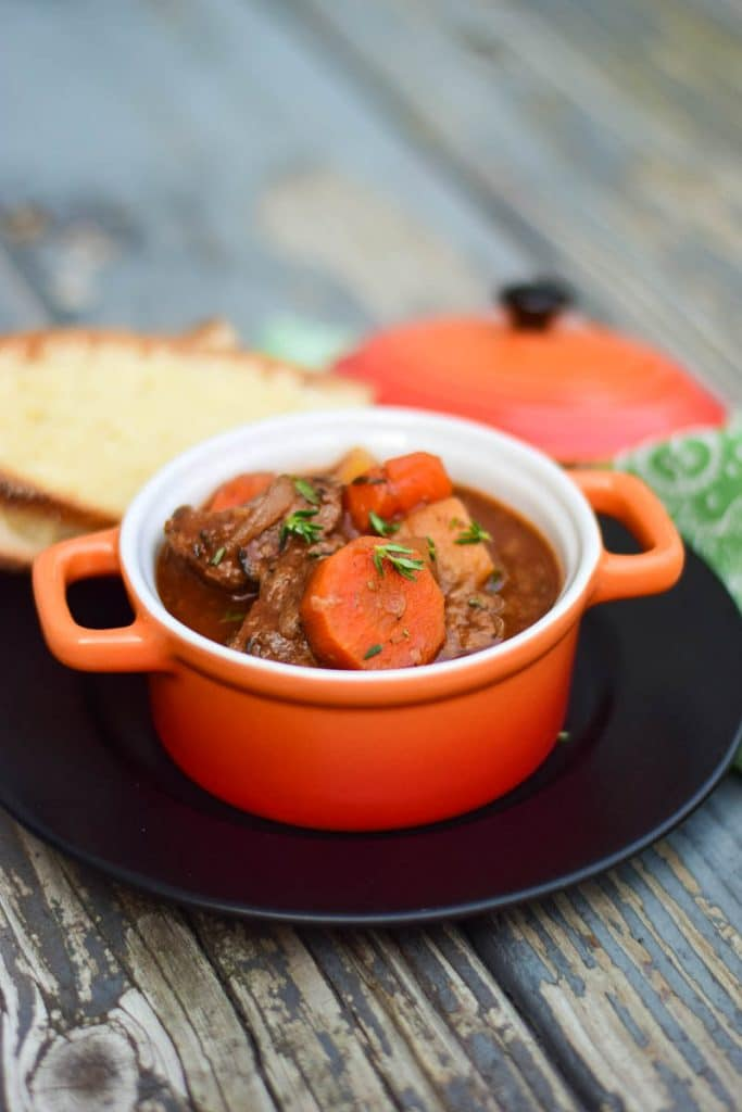 Slow cooked venison stew in an orange crock with slices of homemade bread in the background