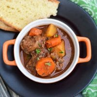Overhead Crockpot Venison Stew in serving dish with bread on the side
