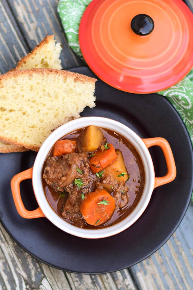 Crockpot Venison Stew in a orange serving crock sitting on a black plate with two slices of homemade bread on the plate and crock lic in background
