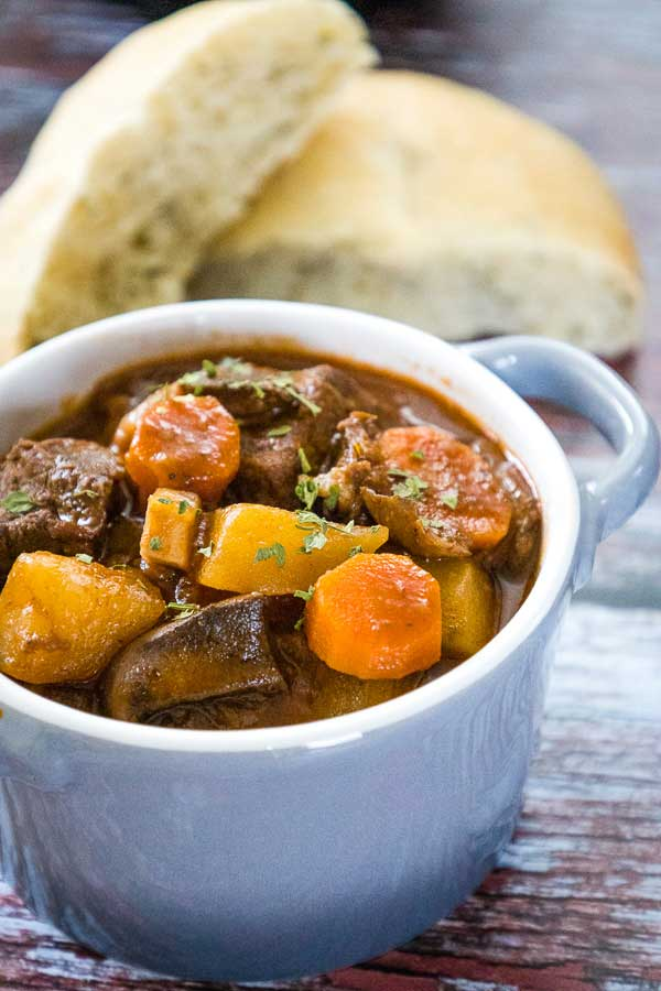 A gray bowl with pieces of venison stew meat, diced potatoes, sliced carrots in a brown broth with fresh thyme on top of the stew and sliced bread blurred in the background