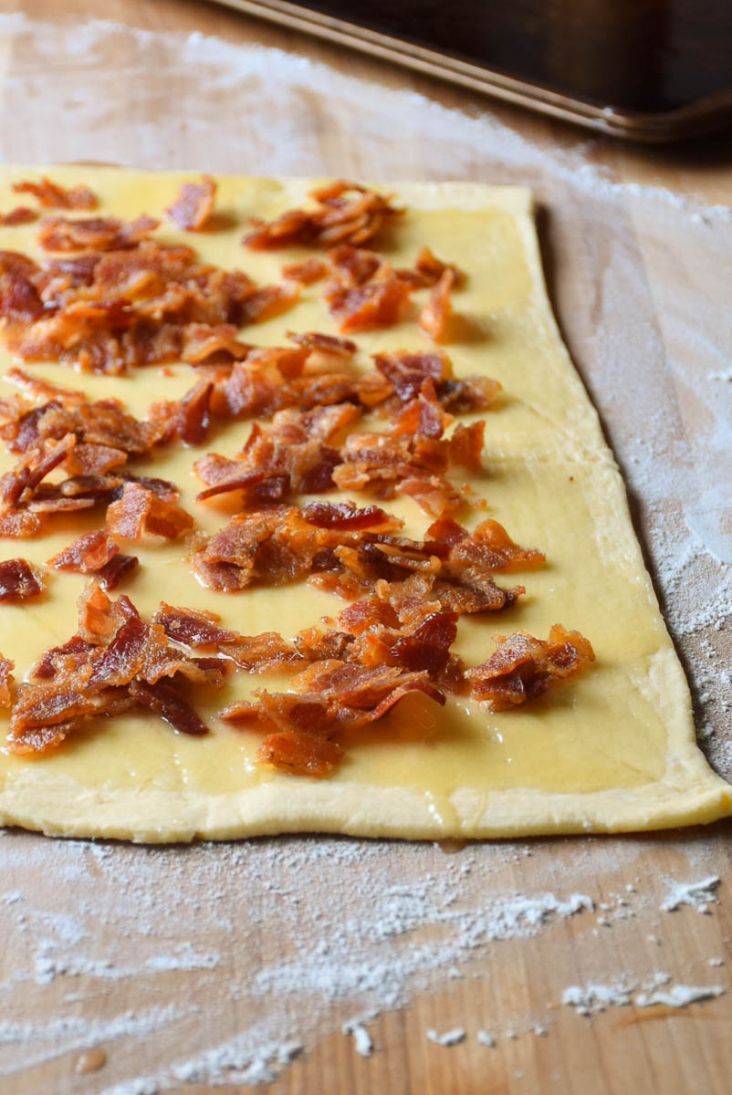 Roll dough spread with maple cream and bacon sprinkled before rolling up