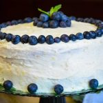 Whole cake on green serving plate decorated with fresh blueberries
