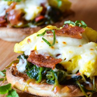 Breakfast Bruschetta in foreground made with a toasted english muffin topped with a tomato spinach base then layered with scrambled eggs, bacon, and cheese