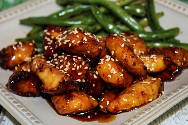 Honey Sesame Chicken on a plate with green bean stir fry