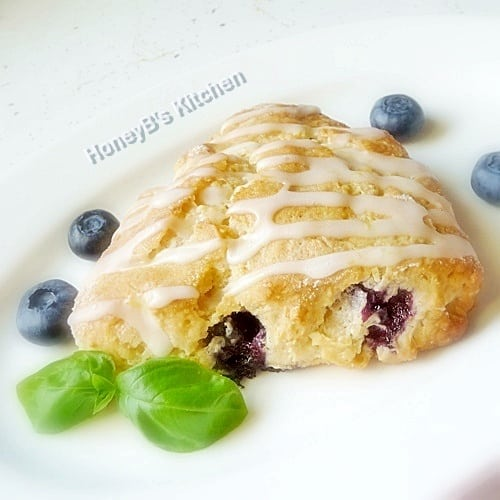 One blueberry scone on a white plate wit fresh blueberries scattered around it