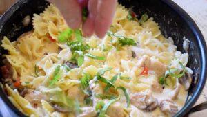 sprinkling basil over finished dish