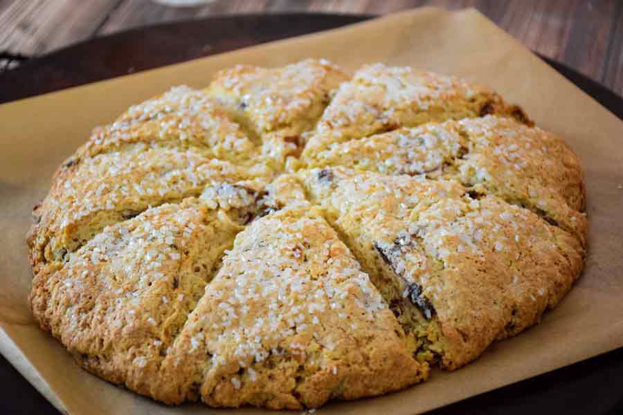 Fully baked and scored date scones on parchment paper