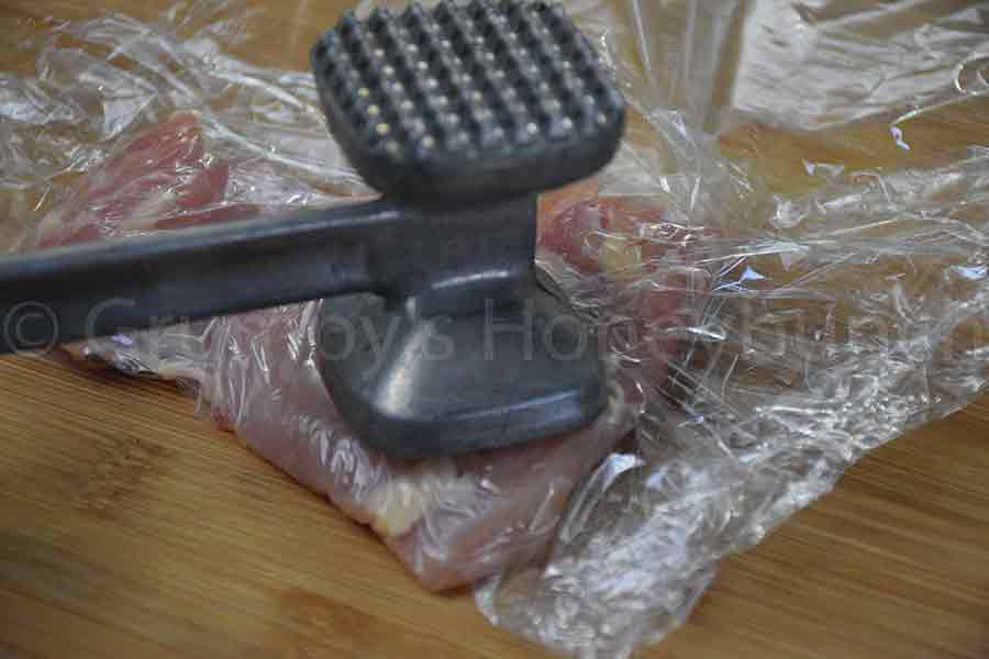 pounding the chicken thighs with a mallet between plastic wrap