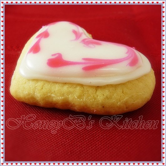 a single heart shaped cookie decorated with glace