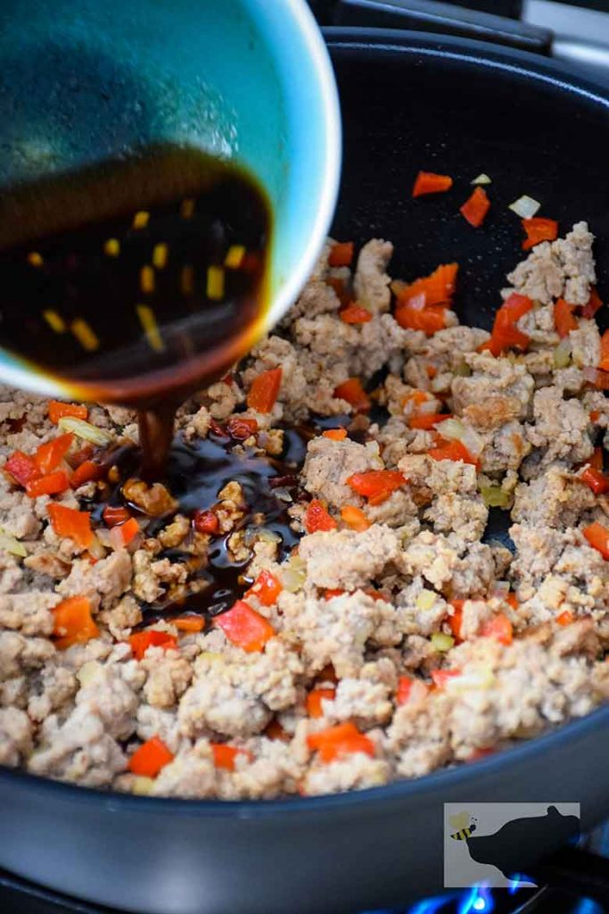 pouring sauce into skillet of browned ground turkey