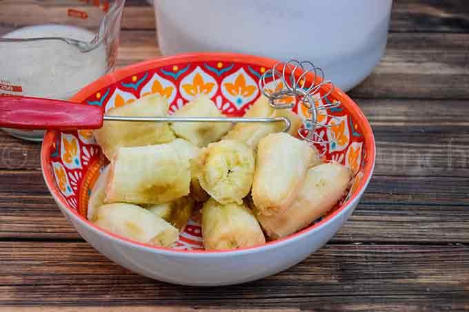 ripe peeled bananas in an orange bowl