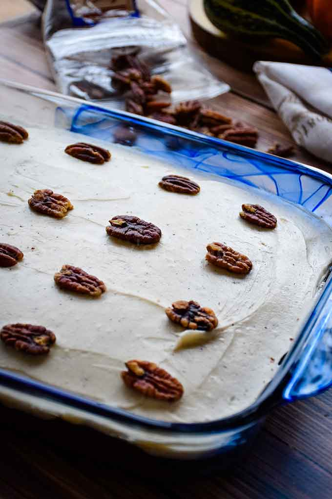 Frosted and decorated with pecans in a blue cake pan