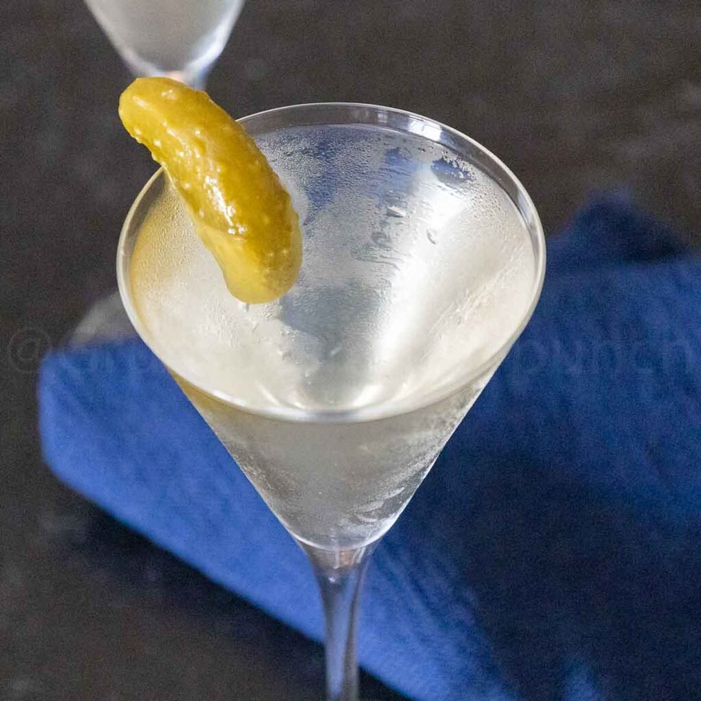 A martini glass filled with a dill pickle martini drink and garnished with a dill pickle.