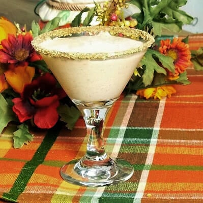 An adult beverage in a martini glass with fall colored foliage in the background