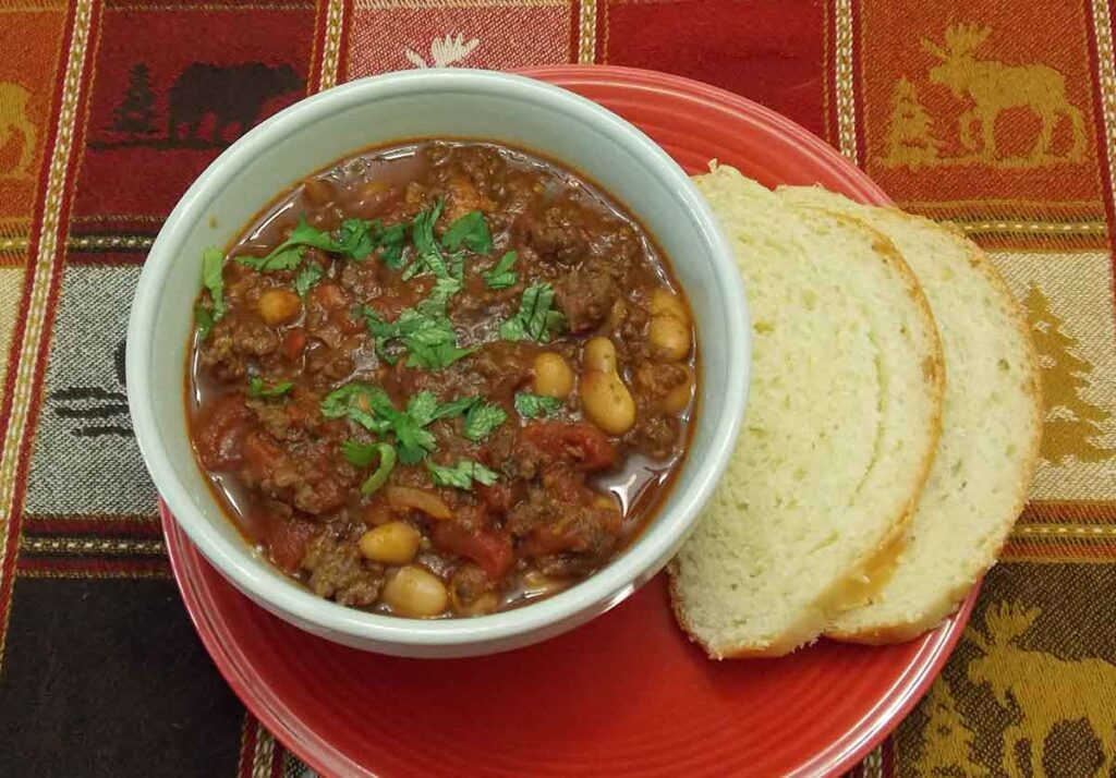 Venison White Bean Chili overhead shot with two slices of white bread on the right hand side