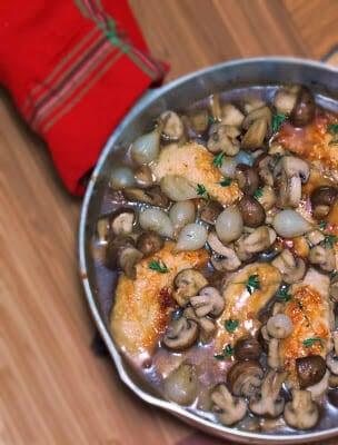 Overhead view of chicken tenders with mushrooms and pearl onions in skilled