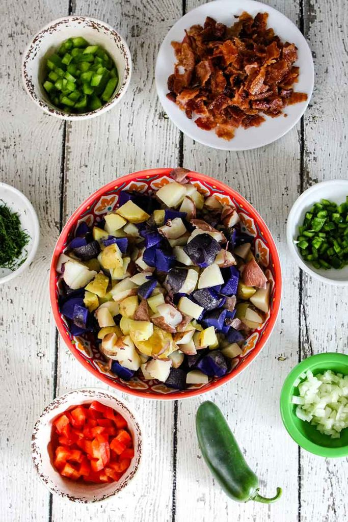A bowl of potatoes in the center of photo with small bowls of chopped vegetables in smaller bowls in a circular pattern