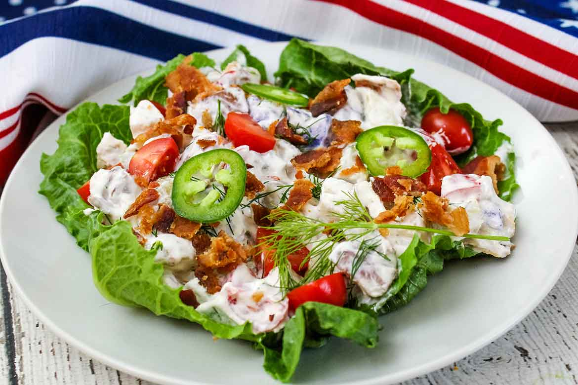 A serving of red, white, and blue potato salad on a white plate with a flag napkin