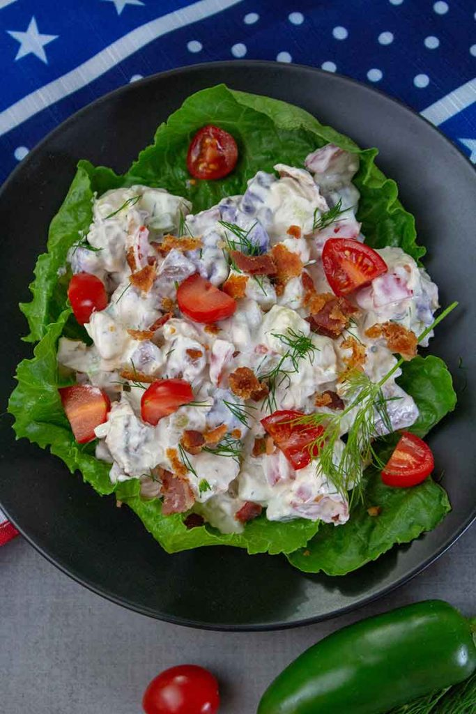Overhead view of a serving of potato salad on a black plate with lettuce beneath the salad. Jalapeno and grape tomato sitting at bottom of plate.