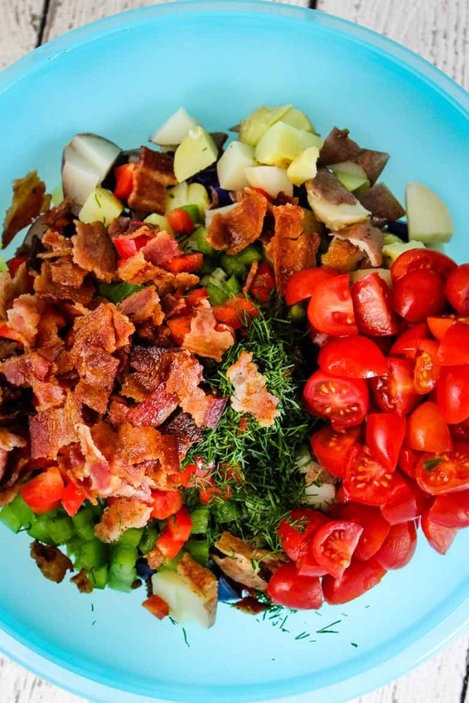 An overhead view of all of the potato salad ingredients in a bowl, before adding dressing