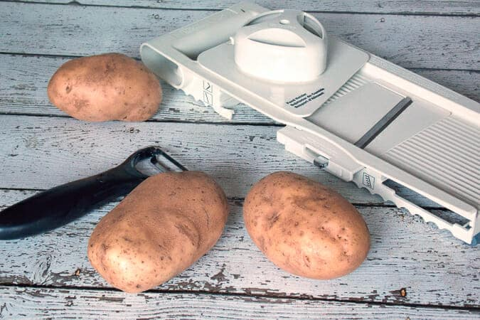 3 potatoes, a potato peeler, and mandolin
