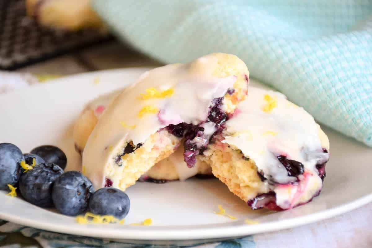 Blueberry Cookies with a lemon glaze on a plate with one broken in half to show the inside of cookie.
