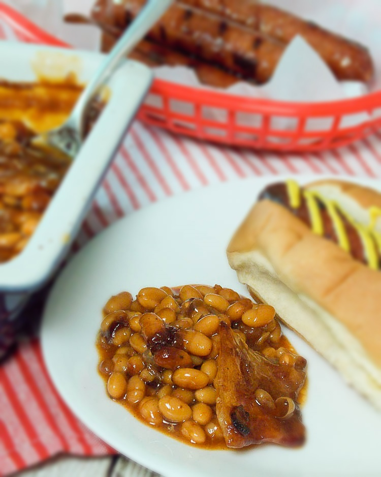 Bourbon Bacon Baked beans on a white plate with a hotdog on the side