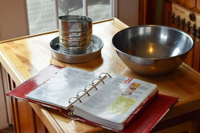 An open cookbook, flour sifter, and mixing bowl on a moveable baking station
