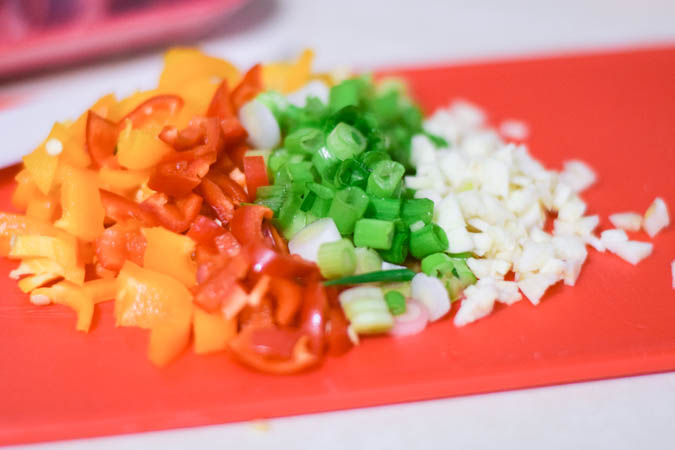 diced peppers, garlic, and onions on a cutting board