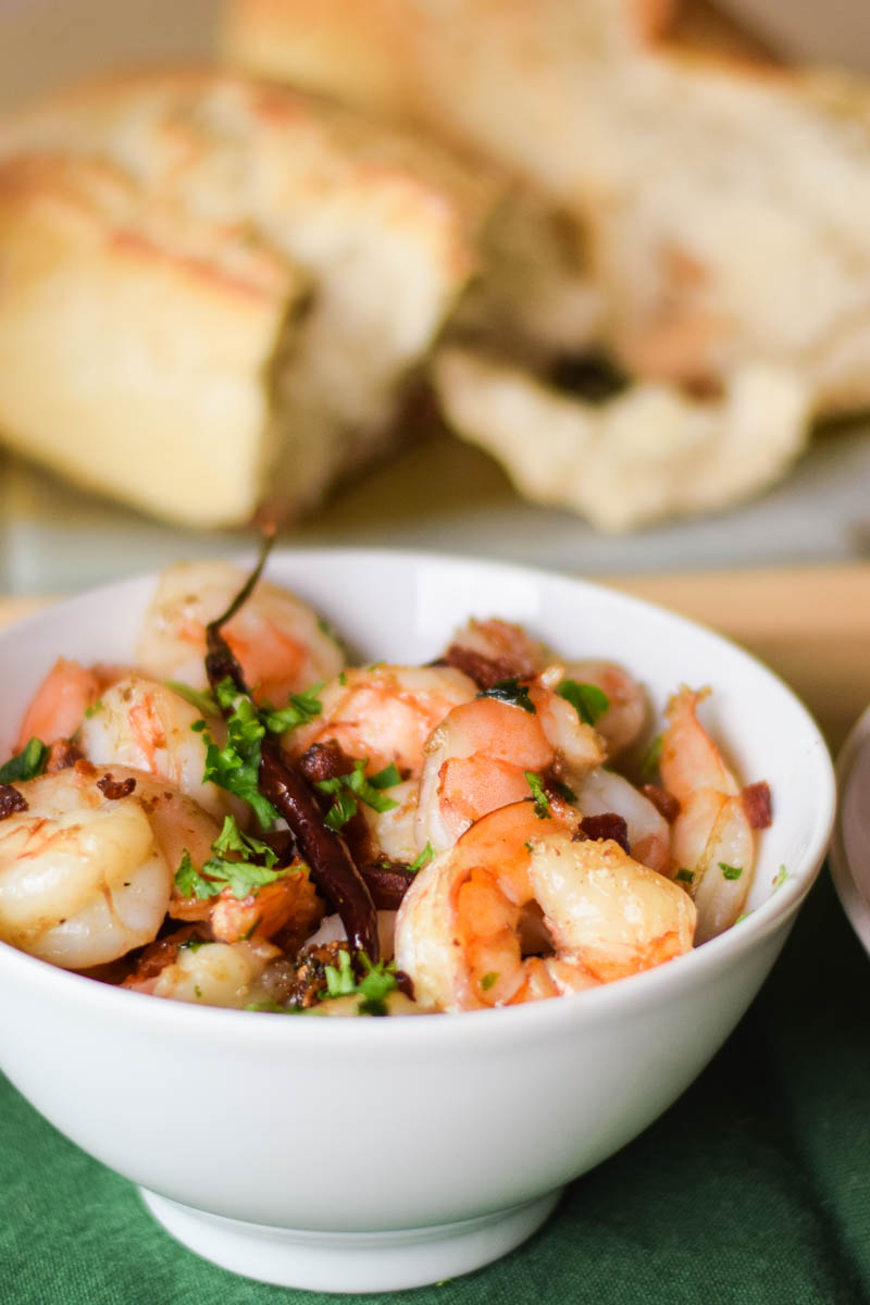 Garlic Shrimp with Pancetta Olive Oil in a white serving bowl topped with chili pepper, pancetta and parsley with a loaf of bread blurred in the background.