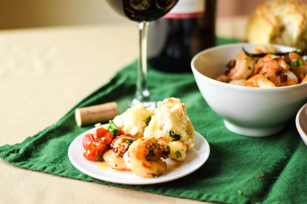 A serving of garlic shrimp with pancetta olive oil on a white plate with a side of roasted tomatoes and bread.